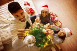 lighthouse-treatment-center-7-tips-for-staying-sober-over-the-holidays-article-image-of-preparations-for-holidays-young-friends-decorating-christmas-tree
