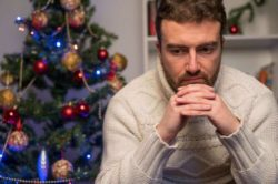 lighthousetreatment-how-to-manage-addiction-triggers-during-the-holidays-article-image-of-man-feeling-depressed-and-lonely-during-the-christmas-time-525688093