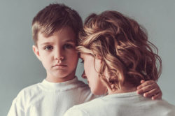lighthousetreatment-5-appealing-rehab-features-for-single-parents-article-photo-cute-little-boy-is-hugging-his-mom-and-looking-sadly-at-camera-on-gray-background-631368539