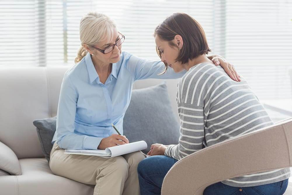 lighthousetreatment-what-can-a-professional-recovery-coach-do-for-you-article-photo-professional-coach-comforting-woman-in-a-clinic-454809682