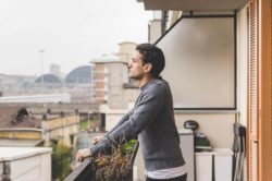 lighthousetreatment-close-to-home-or-far-away-choosing-a-rehab-article-photo-of-young-man-standing-on-a-balcony-outdoor-overlooking-424204705