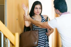 lighthousetreatment-stop-your-addicted-loved-one-from-bullying-you-article-photo-serious-husband-trying-to-stop-girl-leaving-him-at-doorway-417103186