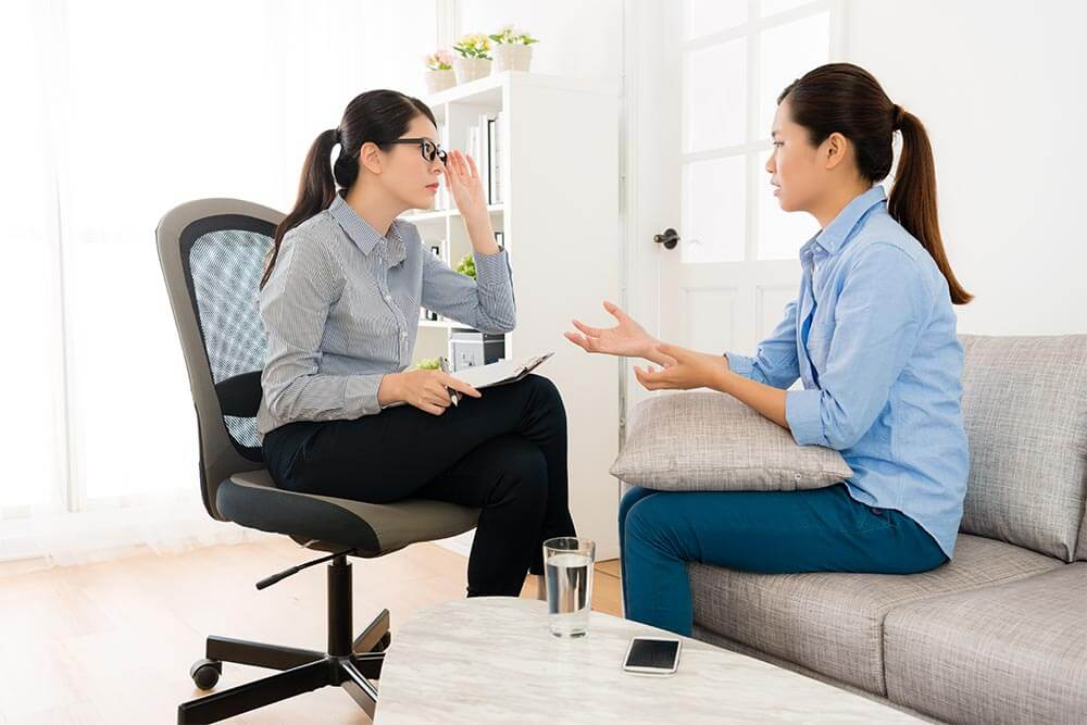 lighthousetreatment-5-questions-to-ask-a-rehab-if-youre-dealing-with-trauma-photo-pretty-elegant-woman-sitting-on-sofa-couch-talking-with-her-doctor-and-psychologist-lady-carefully-672818440