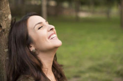 lighthousetreatment-7-tips-for-staying-positive-in-recovery-article-photo-woman-with-happy-expression-relaxing-on-meadow-221790349