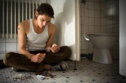 lighthousetreatment-how-long-do-opiates-stay-in-your-system-article-photo-young-man-doing-heroin-in-a-public-toilet-preparing-to-shoot-up-heroin-heating-up-spoon-with-a-642497035