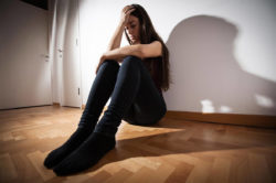 lighthousetreatment-9-ways-to-cope-with-anxiety-without-medication-article-photo-depressed-woman-sitting-on-floor-in-empty-room-790495609