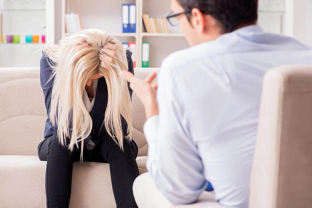 lighthousetreatment-9-ways-to-cope-with-anxiety-without-medication-article-photo-young-woman-visiting-psychiatrist-man-doctor-for-consultation-789421741