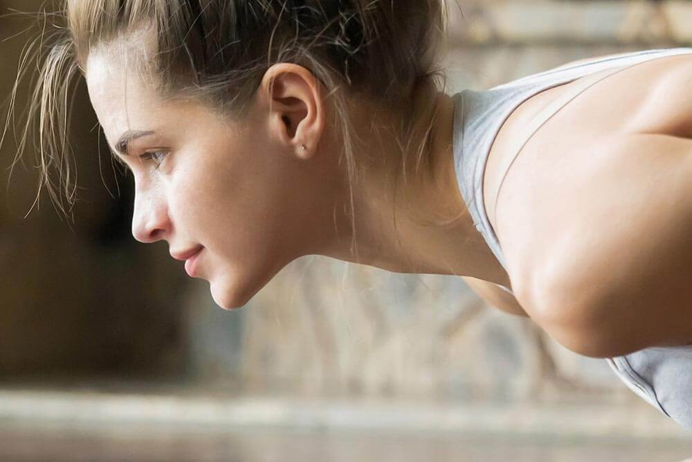 lighthousetreatment-how-to-make-your-new-years-exercise-program-part-of-your-recovery-article-photo-young-woman-doing-yoga-exercise-on-blue-mat-arm-balance-382869562
