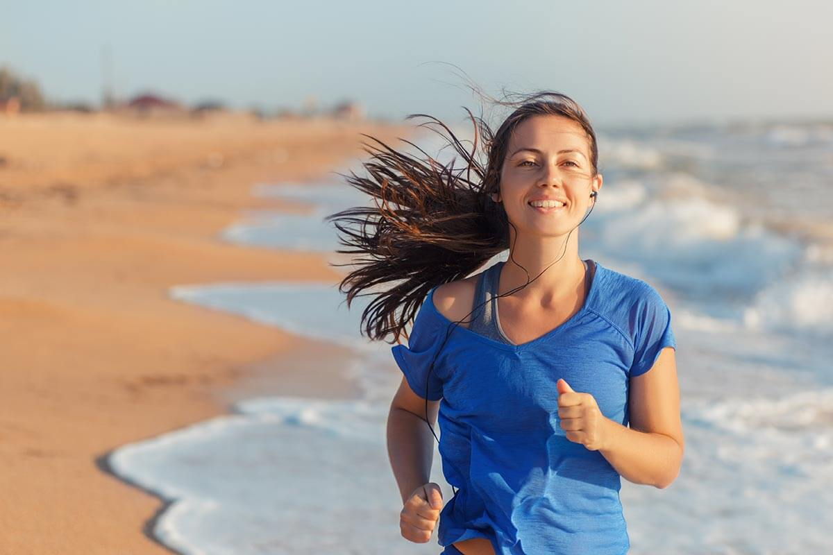 lighthousetreatment-how-to-make-your-new-years-exercise-program-part-of-your-recovery-article-photo-running-woman-on-beach-listening-to-music-in-562641979