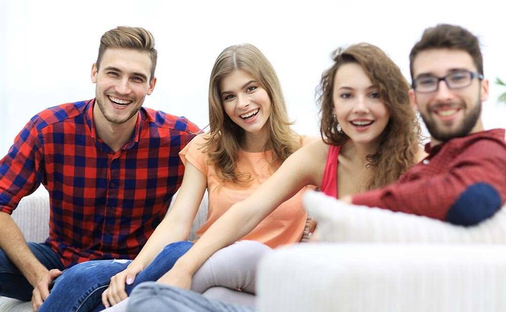 lighthousetreatment-who-really-needs-rehab-what-are-some-alternatives-photo-group-of-cheerful-friends-sitting-on-sofa-717129448