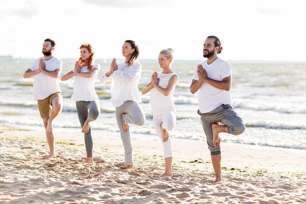 lighthousetreatment-7-ways-to-alleviate-anxiety-without-drugs-article-photo-yoga-fitness-sport-and-healthy-lifestyle-concept-group-of-people-in-tree-pose-on-beach-519449413
