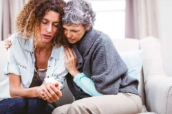 lighthousetreatment-seven-mistakes-loved-ones-make-with-an-addict-article-photo-mother-comforting-tensed-daughter-sitting-on-sofa-at-home-411144139