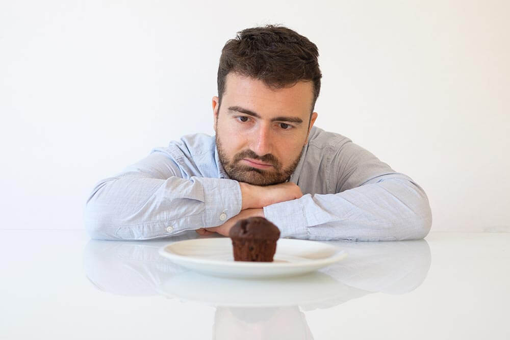 lighthousetreatment-what-should-i-know-about-using-sugar-in-early-recoveryphoto-sweet-tooth-man-on-diet-tempted-by-chocolate-muffin
