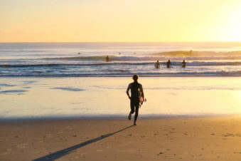 lighthouse-treatment-image-of-surfers-on-beach-502648252