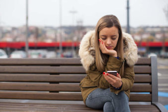 lighthousetreatment-photo-sad-girl-waiting-for-a-phone-call-and-looking-at-mobile-outdoors-756210964