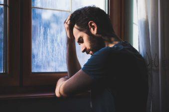 sad drug addicted man standing at a window contemplating his addiction